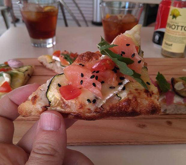 Pizza al corte de salmón, queso brie y calabacín