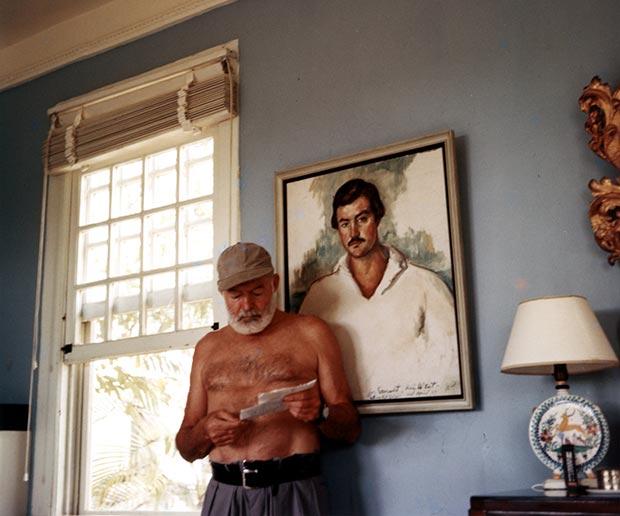 Hemingway en Finca Vigia en 1953 junto a un retrato de el mismo realizado en 1929 por Waldo Peirce