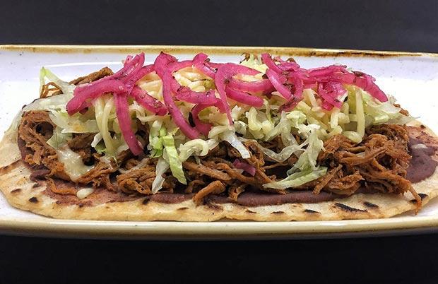 Huarache de chilorio Carne de res desmechada cocinada en chile pasilla y guajillo, frijoles , queso y cebolla morada