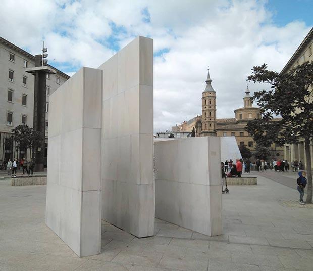 Bloques prismáticos de diferentes dimensiones de hormigón revestidos de mármol blanco, que evocan las tres carabelas en las que embarcó Cristóbal Colón