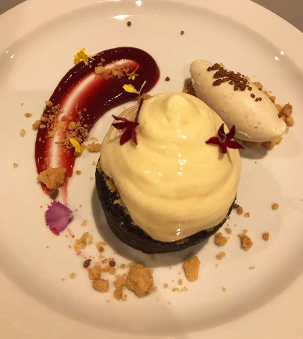 Coulant de chocolate acompañado de espuma de estragón, helado de vainilla, crambel, confitura de frutos rojos y peta zetas