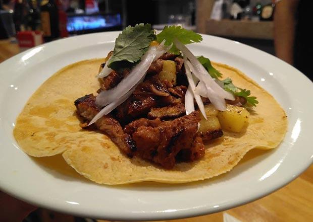 tacos al pastor, que mezclan carne en adobo y piña ahumada