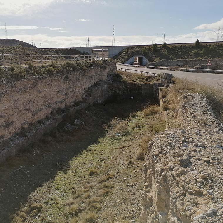 La carretera de Torrecilla, en dirección hacia Valmadrid, pasa por en medio de las esclusas, cortando el antiguo cauce del canal