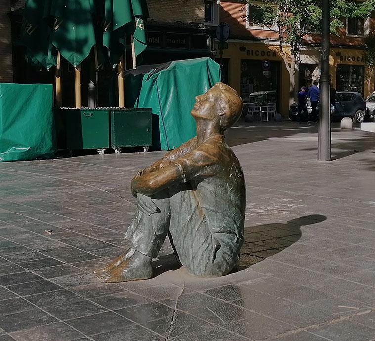 Plaza de San Felipe, donde se encontraba la Torre Nueva. La escultura de un muchacho sentado mira hacia el lugar en que se alzó la torre, señalado por hitos de piedra.