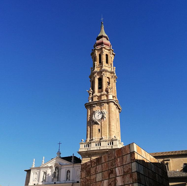 La torre-campanario de La Catedral de San Salvador o La Seo fue proyectada en estilo barroco romano en 1683 por el arquitecto Giovanni Battista Contini para sustituir a la antigua torre mudéjar