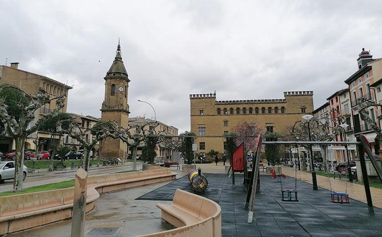 Vista de la plaza Ramón y Cajal de Ayerbe, con la torre del Reloj (izquierda) y el Palacio de los Marqueses de Urriés o de Ayerbe (derecha)
