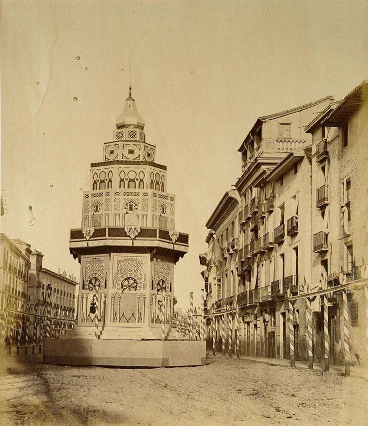 """obelisco efímero de gusto árabe, decorado con los atributos de la agricultura, de la industria y del comercio, en elegantes transparentes"""", erigido en el Coso"""