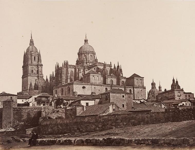 Fotografía de la Catedral Nueva de Salamanca. Los principales rasgos de la Catedral son las dos torres góticas que dominan el horizonte. Alrededor de la base de la Catedral hay edificios domésticos. Un pequeño grupo de personas están sentadas en un muro a la izquierda en primer plano.