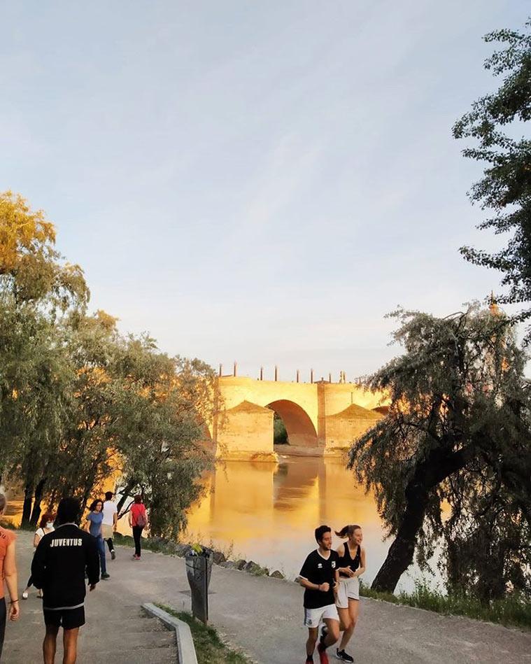 Ciudadanos paseando o haciendo ejercicio en el entorno del Puente de Piedra, este sábado