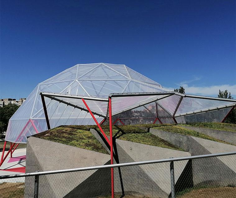 La cubierta de hormigón de La Cúpula Geodésica se integra con el talud verde del parque y permite contener las tierras sobre el escenario