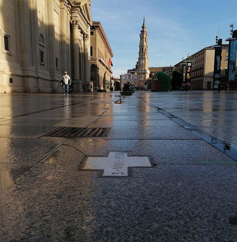 Una pequeña cruz sobre el pavimento muestra el lugar exacto de la plaza del Pilar en el que cayó una bomba el 3 de agosto del año 1936