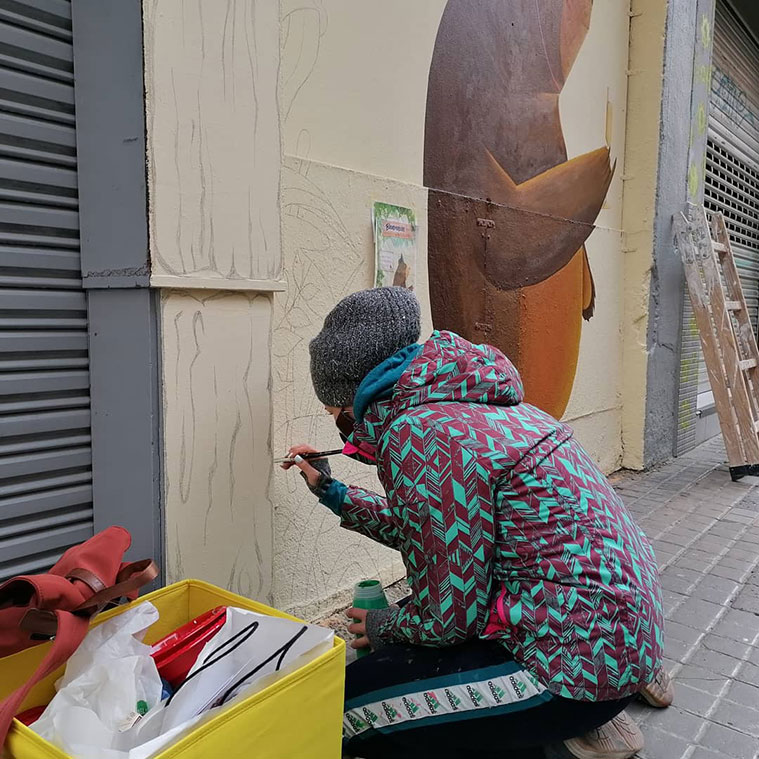 La artista Verónica Martínez trabajando en uno de los murales del proyecto Rúa Feliz de la Calle San Antonio María Claret